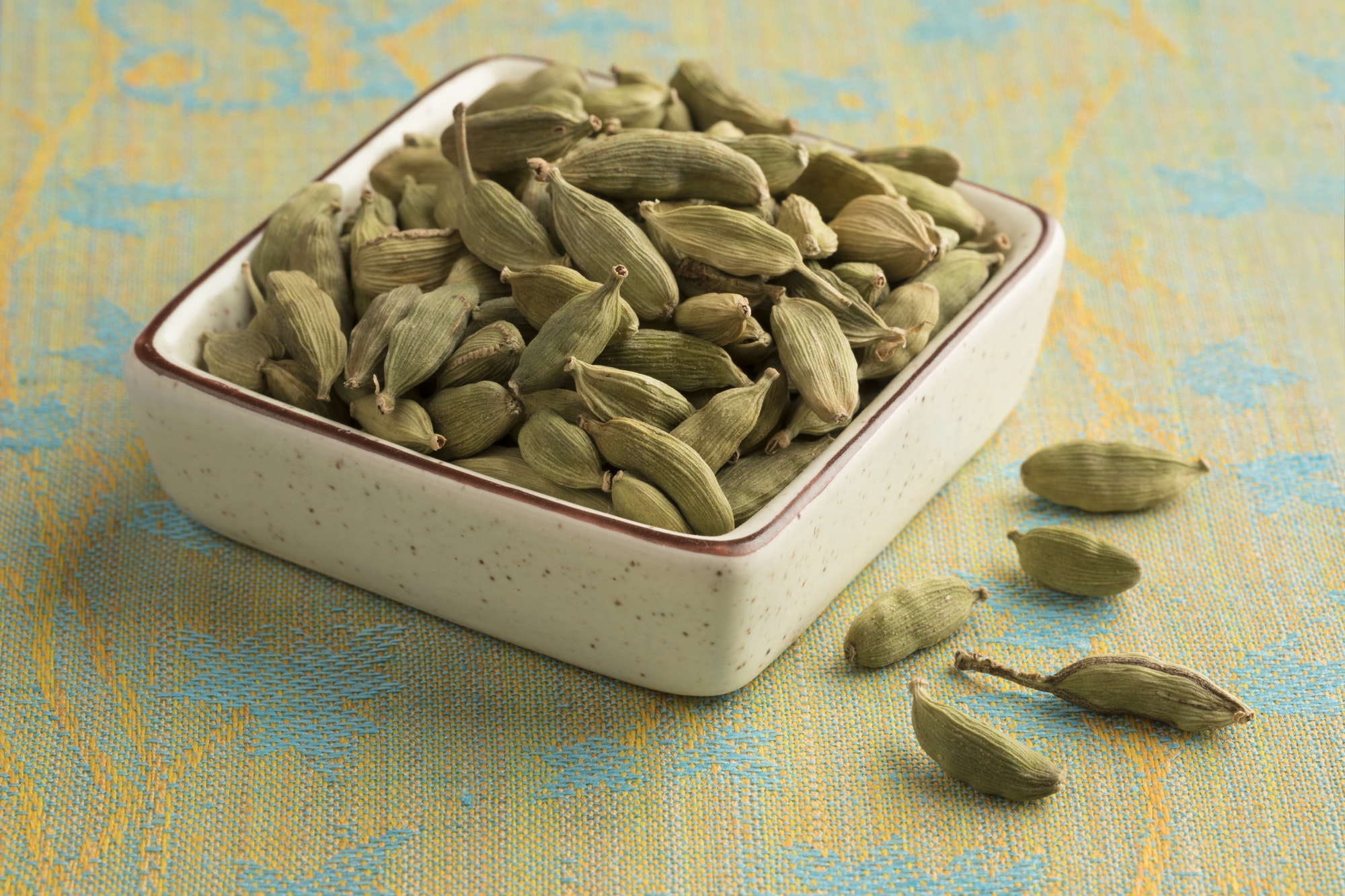 Bowl with green cardamom pods