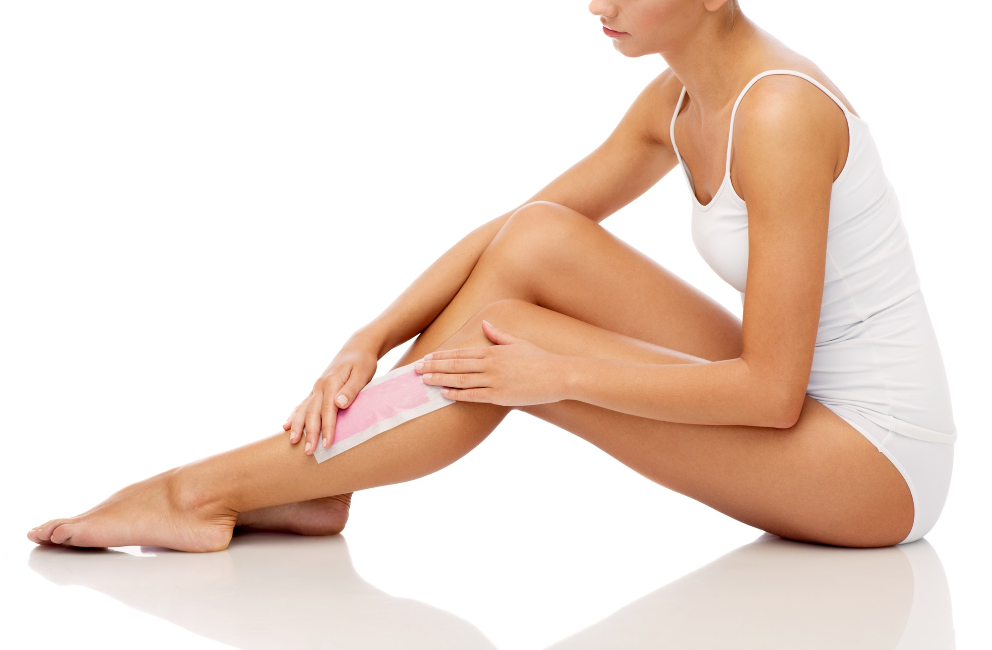 woman removing leg hair with depilatory wax strip