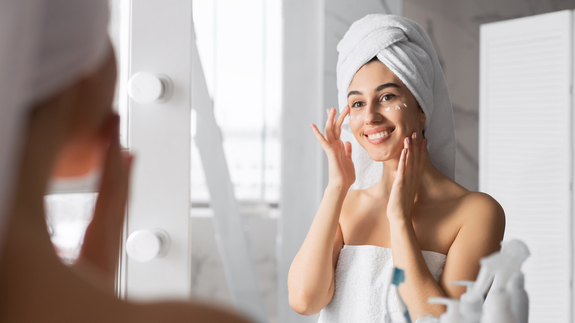 Woman Applying Eye Cream Taking Care Of Skin In Bathroom