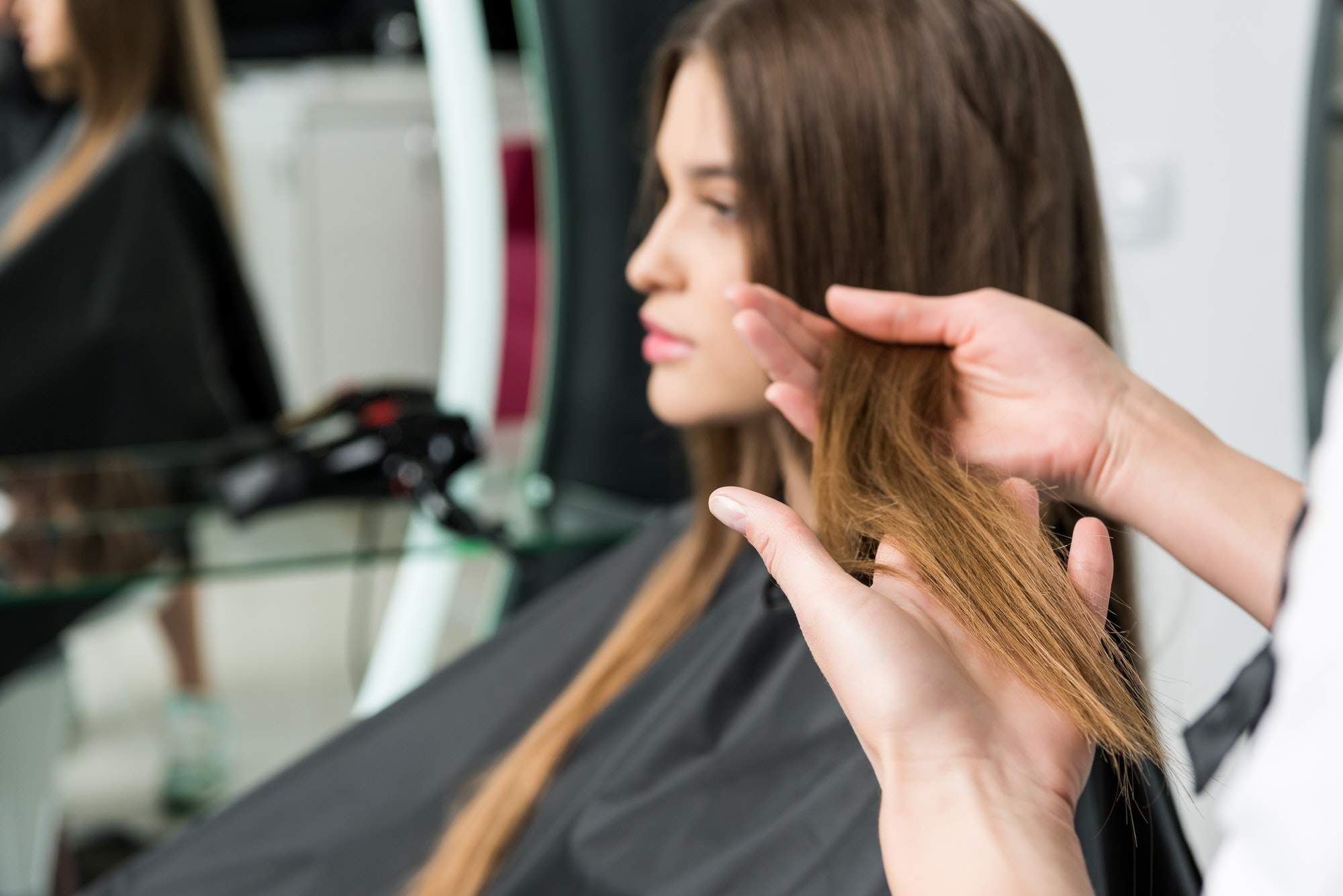 young woman with beautiful hair in hair salon